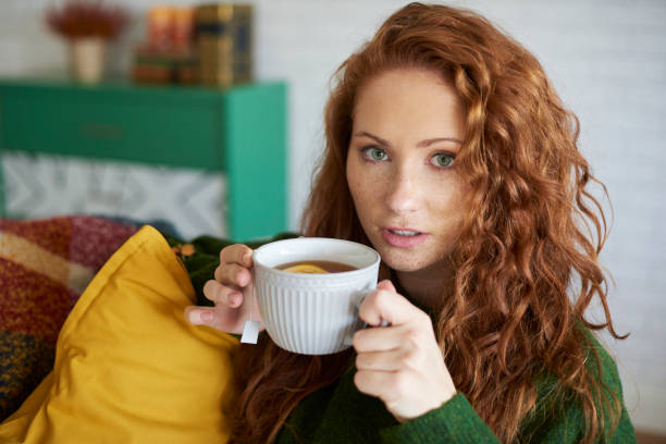 portrait der schönen frau zu hause tee trinken - heiße zitrone stock-fotos und bilder