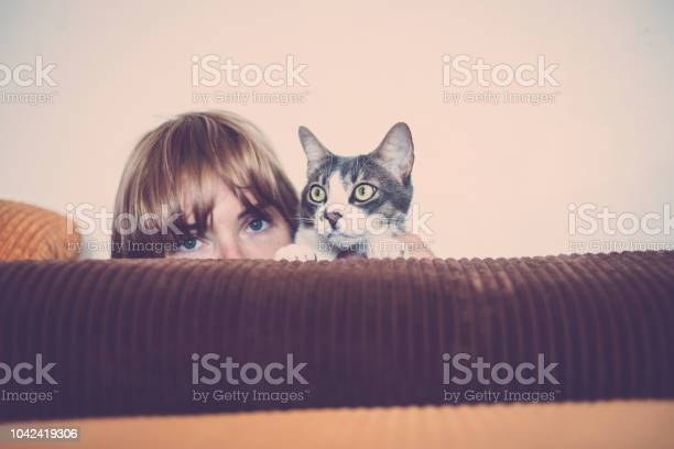 Portrait of beautiful woman hidden behind the sofa with her cat at picture id1042419306?b=1&k=6&m=1042419306&s=612x612&h=g phfv9z pf3grjh96pirilj fbdpdyinja4vegx 4e=