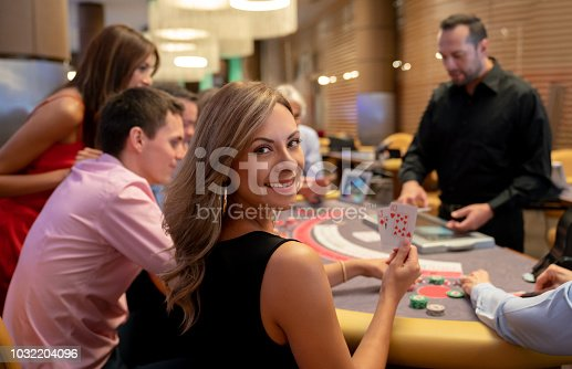 Portrait of beautiful woman holding the winning cards at the blackjack table in the casino