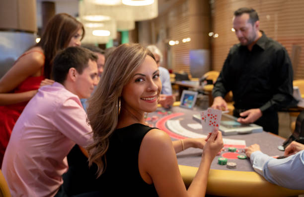 Portrait of beautiful woman holding the winning cards at the blackjack table while looking at camera smiling Portrait of beautiful woman holding the winning cards at the blackjack table in the casino game of chance stock pictures, royalty-free photos & images