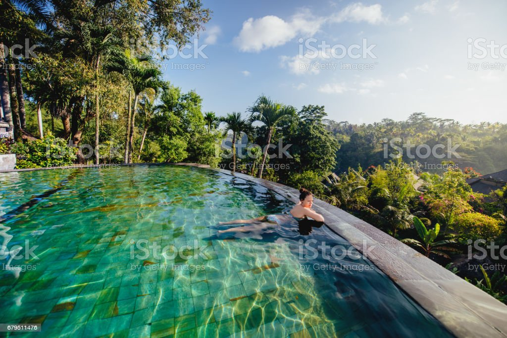 portrait of beautiful woman in luxurious resort. Young girl taking a bath and relaxing at infinity swimming pool royalty-free stock photo