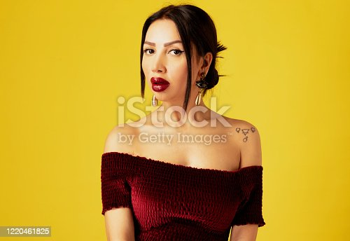 Portrait of beautiful woman in red velvet strapless front of yellow background. She is looking at camera.