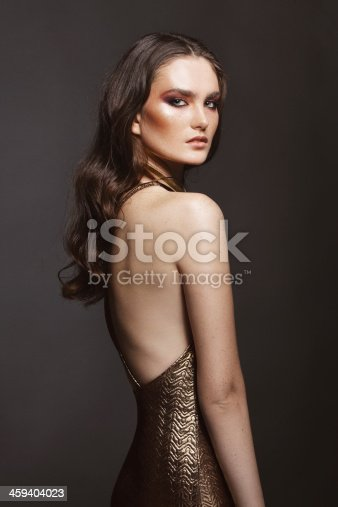 Studio portrait of woman with freckles. She's wearing golden dress. Professional make-up and hairstyle. High-end retouch.