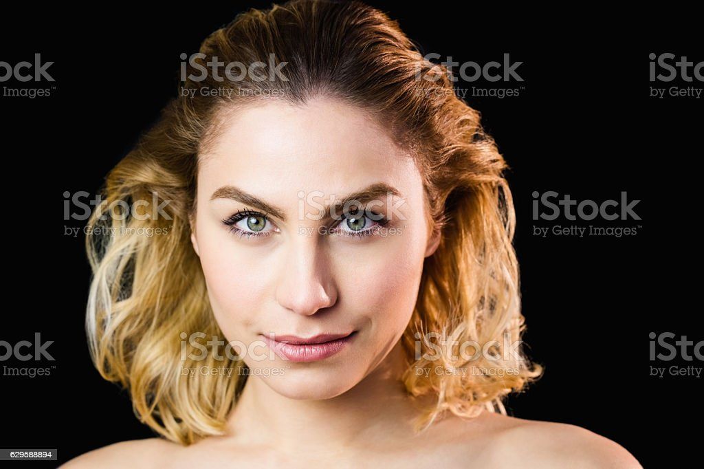 Portrait of beautiful woman posing against black background stock photo