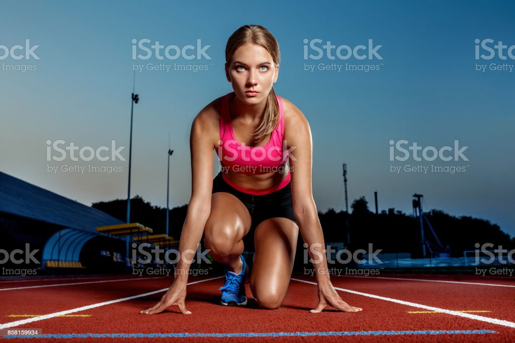 Portrait of beautiful woman ready to start running stock photo