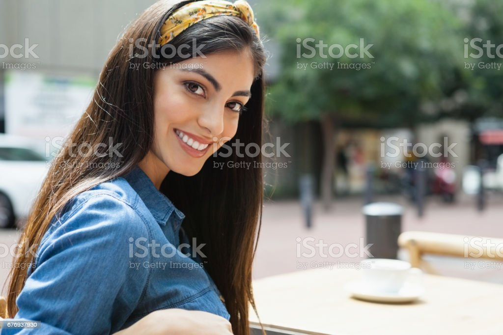 Portrait of beautiful woman sitting on chair at sidewalk cafe stock photo