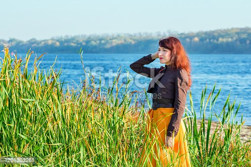 Portrait of beautiful smiling brunette woman, wearing stylish brown jacket and yellow skirt, standing on the river bank.