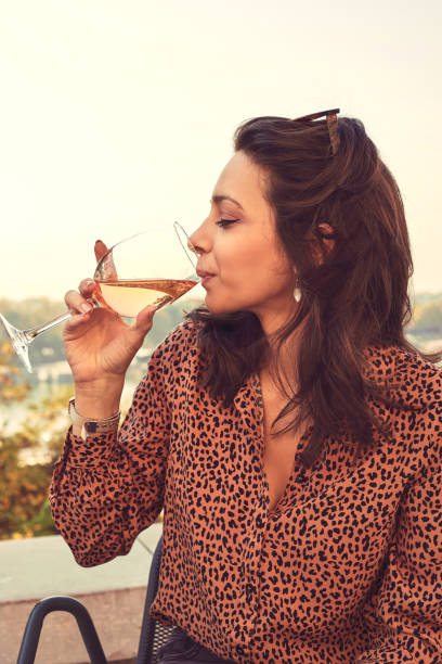 Portrait of beautiful woman using cellphone and drinking wine outdoors. stock photo