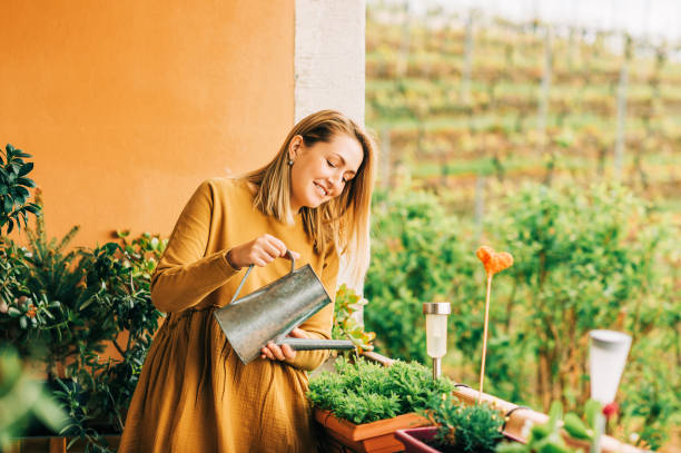 Porträt von schönen Frau wässern grüne Pflanzen auf dem Balkon, trägt braune Baumwollkleid – Foto