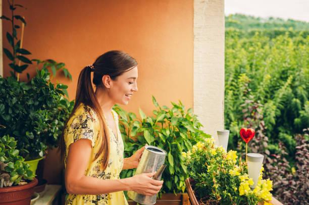 Porträt der schönen Frau wässern grüne Pflanzen auf dem Balkon, kleinen gemütlichen Garten in der Wohnung – Foto