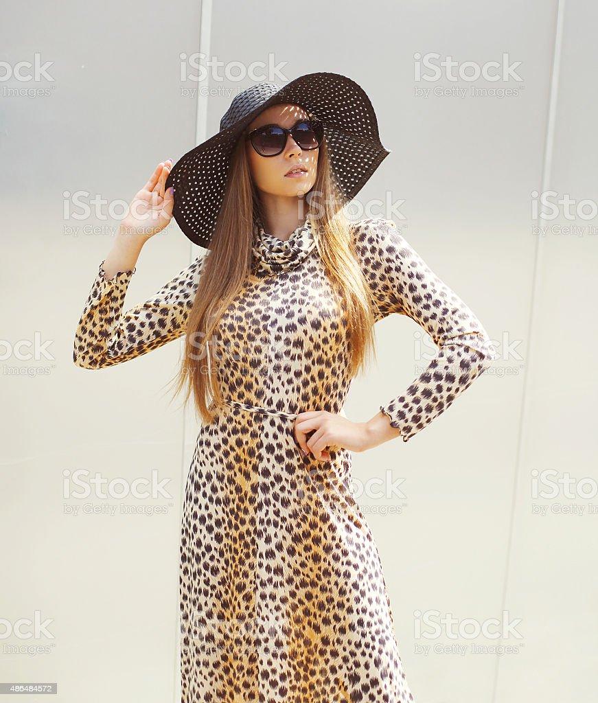 Portrait of beautiful woman wearing a leopard dress, straw hat stock photo