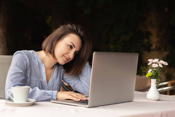 Portrait of beautiful woman who works from home, she sits with a cup of coffee at the table, working on laptop indoors stock photo