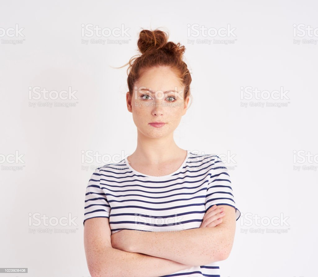 Portrait of beautiful woman with arms crossed at studio shot stock photo
