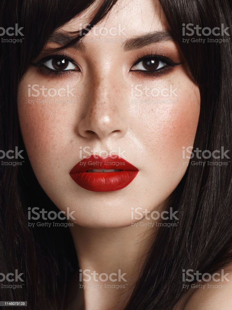 Close-up portrait of beautiful woman with cat eye make-up and red...