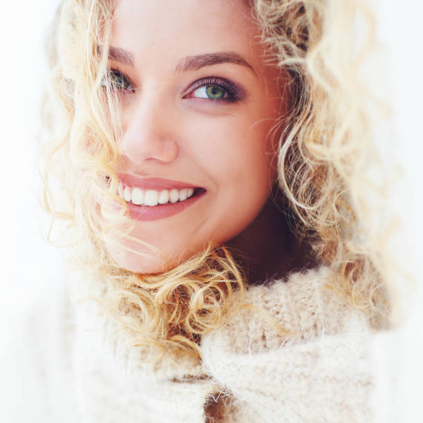 portrait of beautiful woman with curly hair and adorable smile stock photo