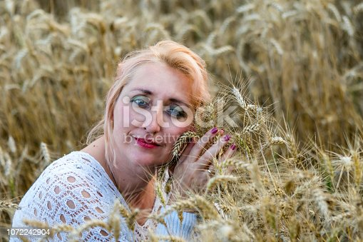 977601820 istock photo Portrait of beautiful woman with green eyes sitting in golden wheat field and hold bunch of wheat ears. Liberty, love, happy summer, peace of mind or agriculture concept. 1072242904
