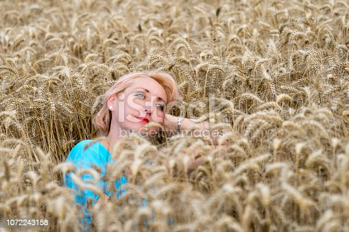 977601820 istock photo Portrait of beautiful woman with green eyes sitting in golden wheat field and look in the sky. Liberty, love, happy summer, peace of mind or relaxation concept. 1072243158