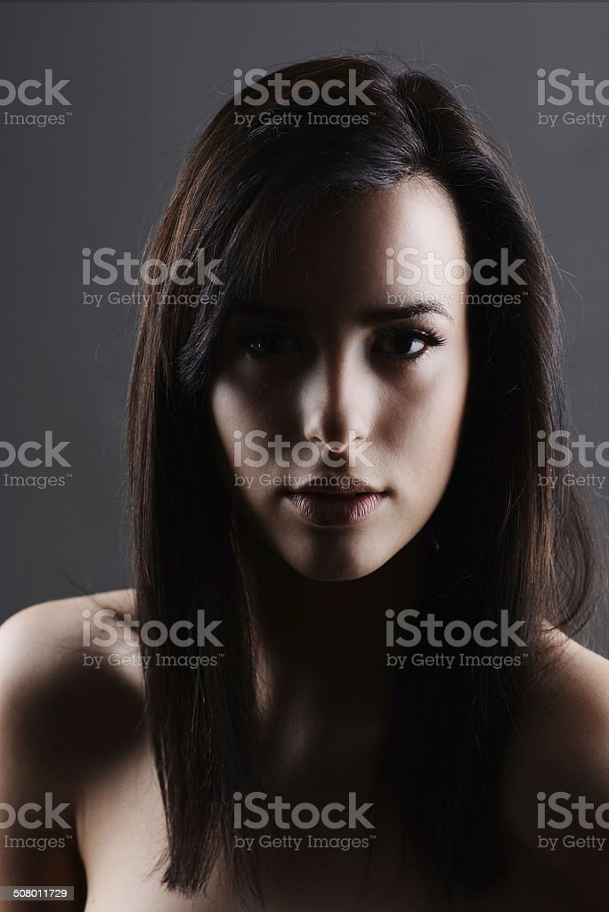 Portrait of beautiful woman with smooth skin, nude in shadows - Stock image  .
