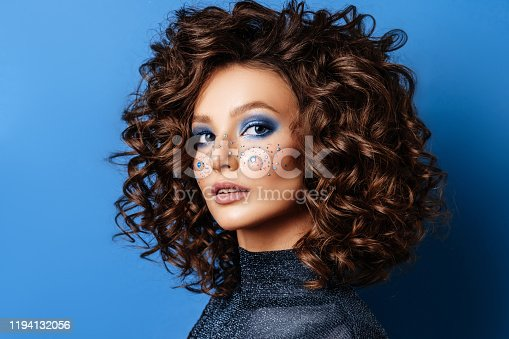 Portrait of Beautiful Woman with Sparkles on her Face. Fashion Model with Colorful Makeup