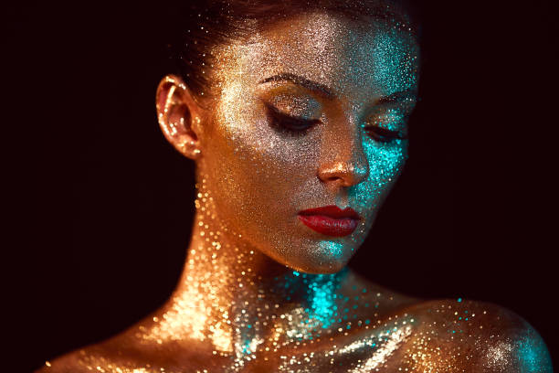 Portrait of beautiful woman with sparkles on her face Portrait of Beautiful Woman with Sparkles on her Face. Girl with Art Make-Up in Color Light. Fashion Model with Colorful Makeup stage make up stock pictures, royalty-free photos & images