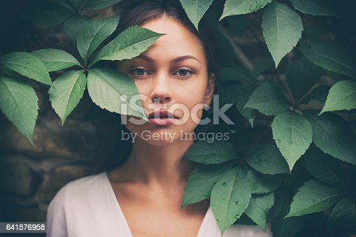 Portrait of beautiful fashion model looking at camera from the green leaves of big plant. She has no make up. She wears a white shirt and looks amazing.