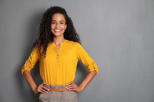 Portrait of young african woman standing with hands on waist and looking at camera. Confident stylish latin girl standing against grey background. Happy young mixed race woman smiling isolated on gray wall with copy space.