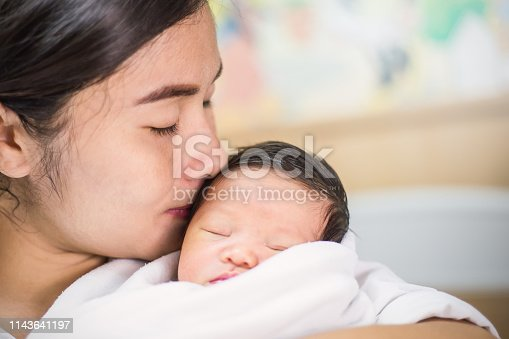 Portrait of beautiful young asian mother kissing  her newborn baby, copy space with bed in the hospital background.