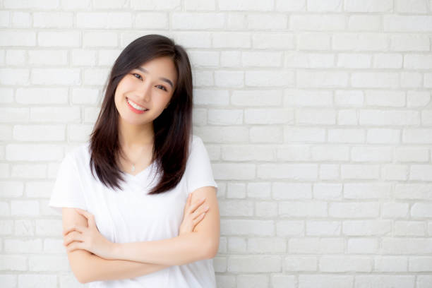 portrait of beautiful young asian woman happiness standing on gray cement texture grunge wall brick background, businesswoman is a smiling on concrete, business people concept. - ásia imagens e fotografias de stock