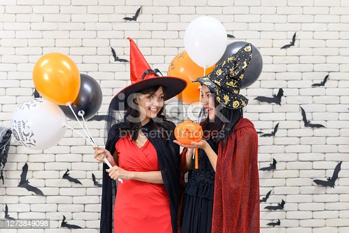 Portrait of beautiful young asian woman wearing witch costume holding pumpkin Jack O Lantern and balloon on background decorated for Halloween