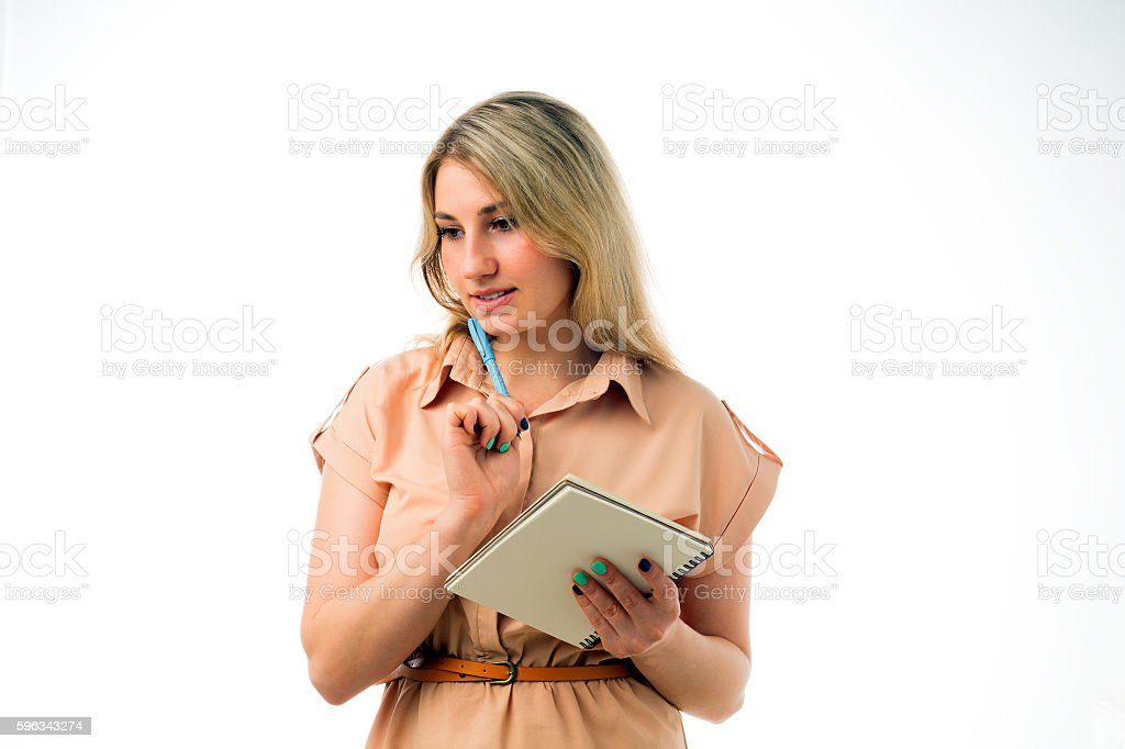 Portrait of beautiful young blonde woman thinking with a notepad royalty-free stock photo
