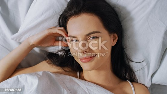 istock Portrait of Beautiful Young Brunette Charmingly Sleeping in Her Bed at Night in the Dark Room. Sweet and Warm View of Girl Sleeping Calmly. Top Down Shot. 1162082435