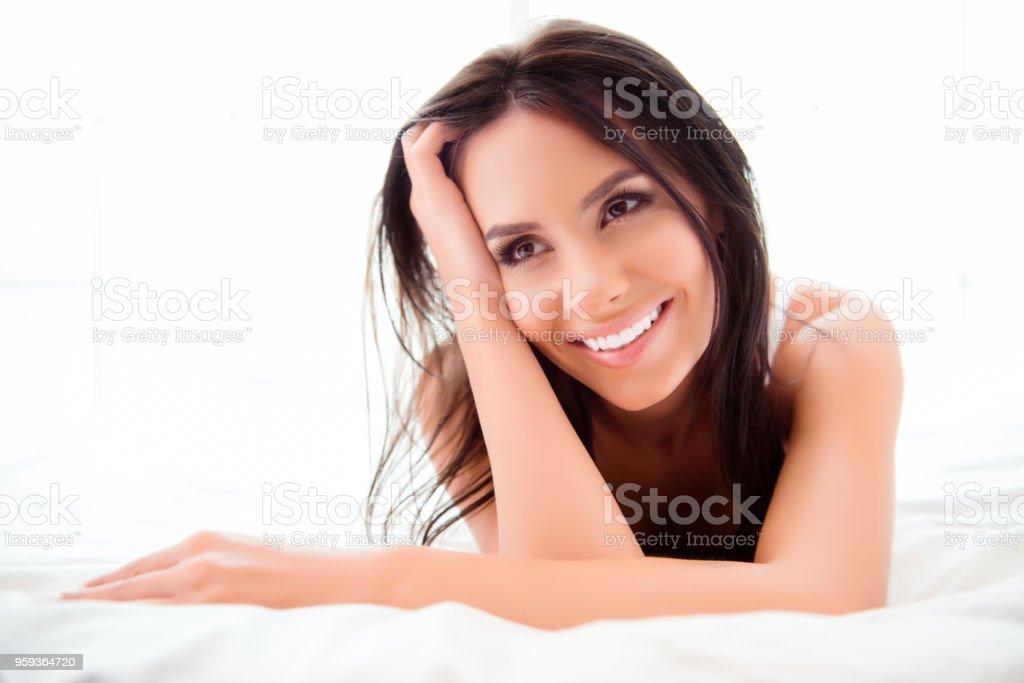 Brunette lying on bed