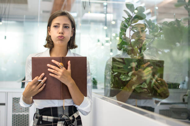 Portrait of beautiful young business woman pouting and holding notebook in office stock photo