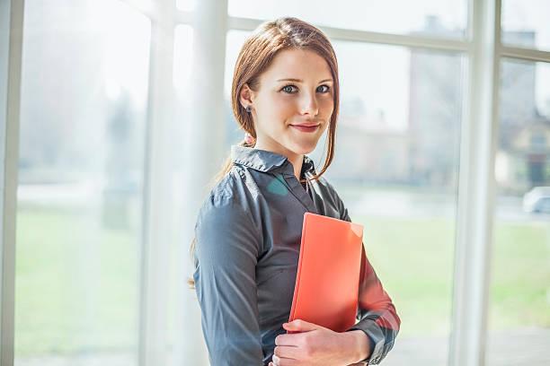 Porträt von schöne junge Geschäftsfrau halten Ordner im Büro – Foto
