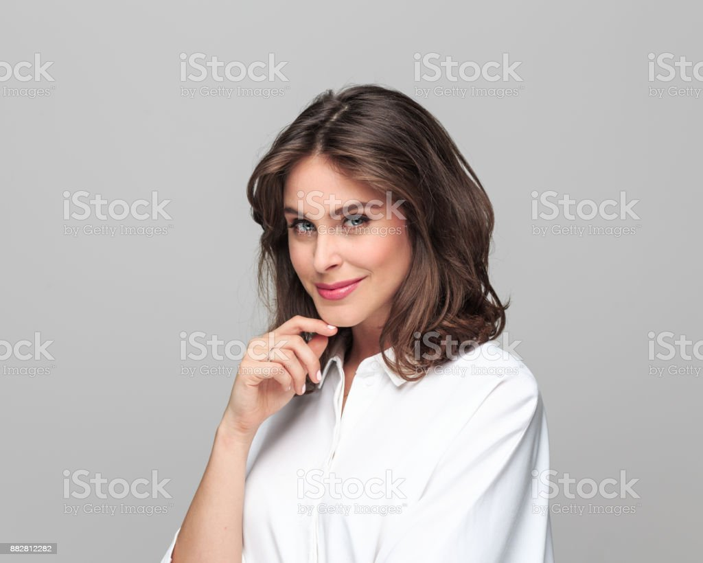 Portrait of beautiful young businesswoman Portrait of beautiful young businesswoman standing with her hand on chin and looking at camera against grey background. 25-29 Years Stock Photo