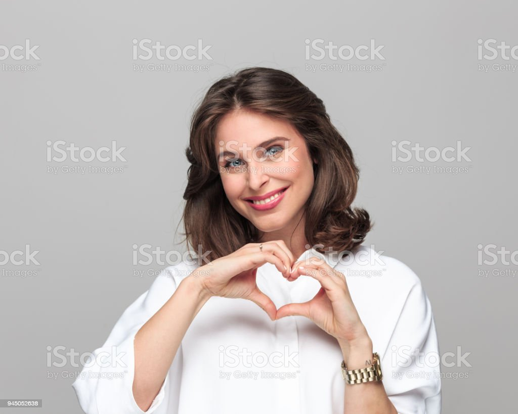 Portrait of beautiful young businesswoman Portrait of beautiful young businesswoman smiling at camera against grey background, gesturing heart shape with her fingers. 25-29 Years Stock Photo