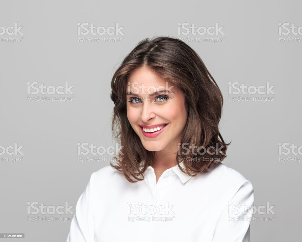 Portrait of beautiful young businesswoman Portrait of beautiful young businesswoman smiling at camera against grey background. 25-29 Years Stock Photo