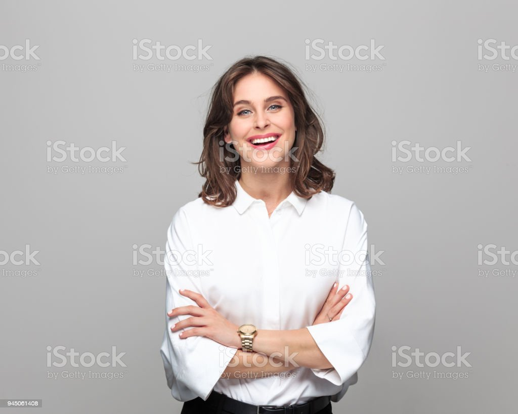 Portrait of beautiful young businesswoman Portrait of confident young businesswoman standing with hand crossed and smiling against grey background. 25-29 Years Stock Photo