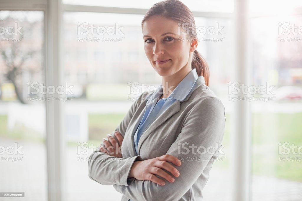 Portrait of beautiful young businesswoman standing arms crossed in office stock photo