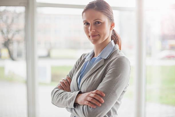 Porträt von schöner junger Geschäftsfrau stehend Arme verschränkt im Büro – Foto