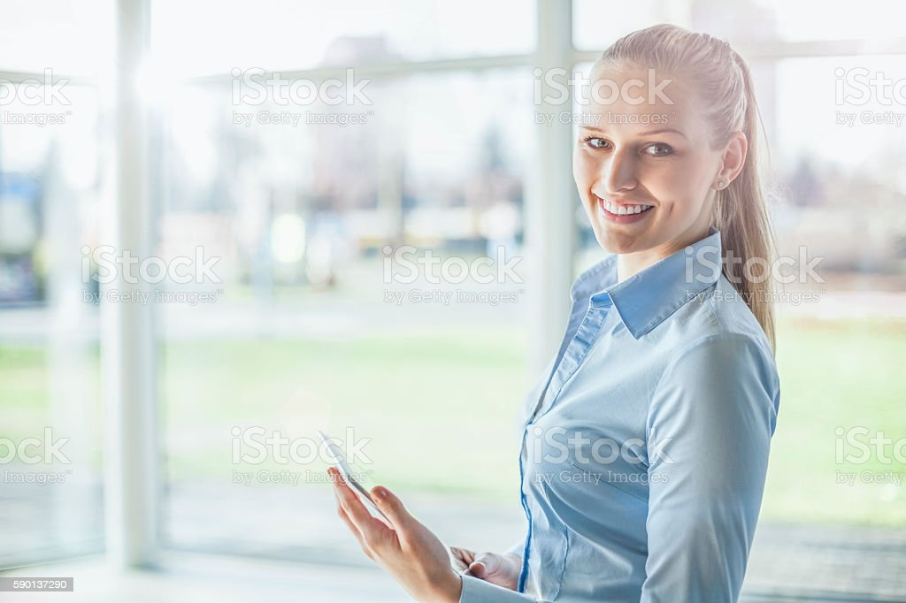 Portrait of beautiful young businesswoman using digital tablet in office – Foto