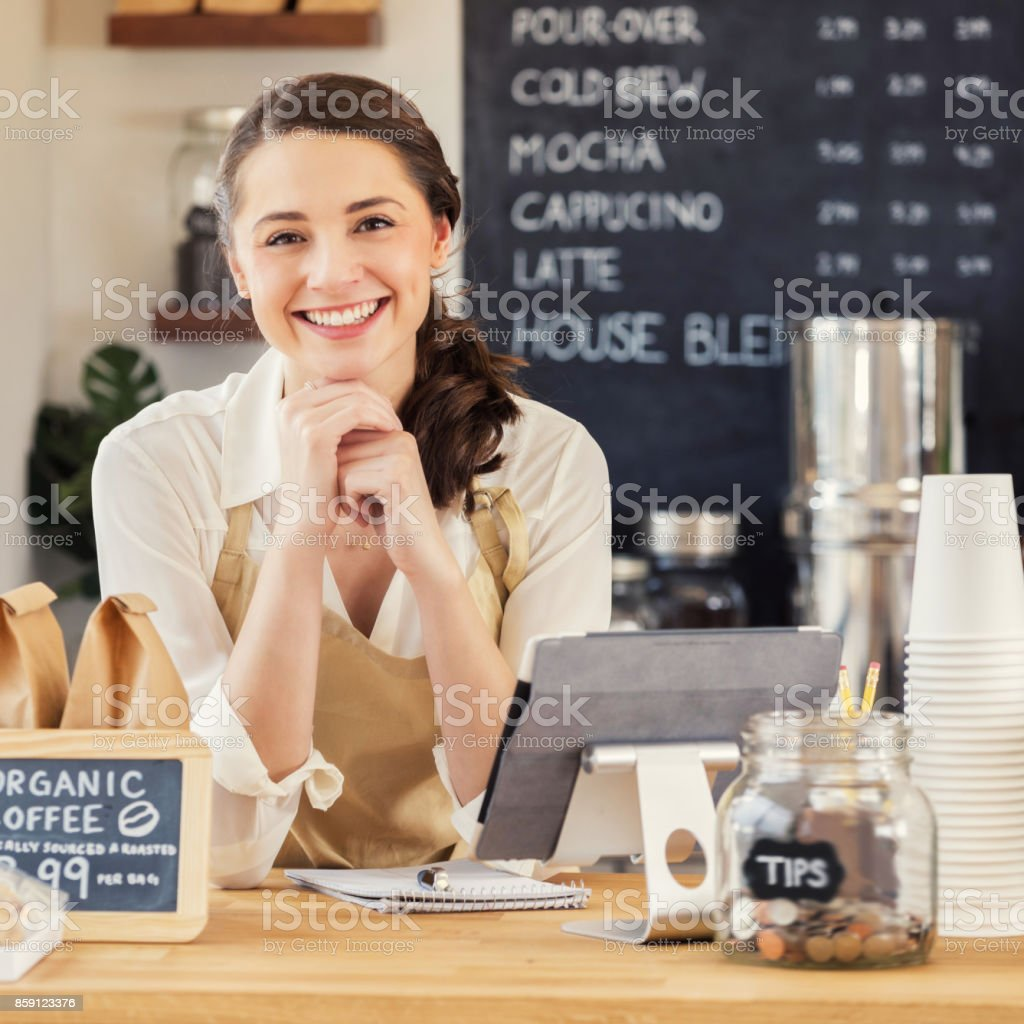 Portrait of beautiful young coffee shop owner leaning proudly on counter stock photo
