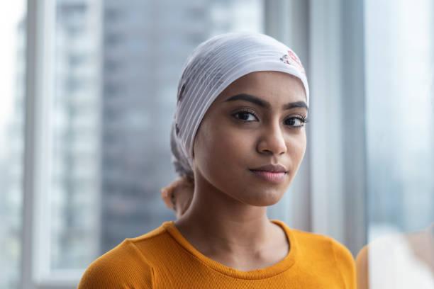 portrait of beautiful young ethnic woman with cancer - sopravvivenza foto e immagini stock