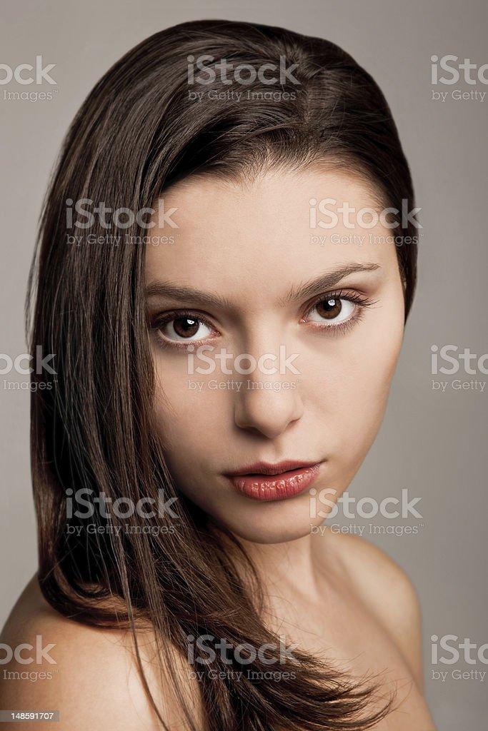 Portrait of beautiful young female model against brown background royalty-free stock photo