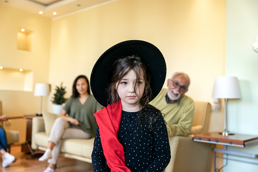 Young Elegant Girl is Posing in Fashion Style with Large Black Hat and Red Scarf and Feeling Happy and Satisfied.