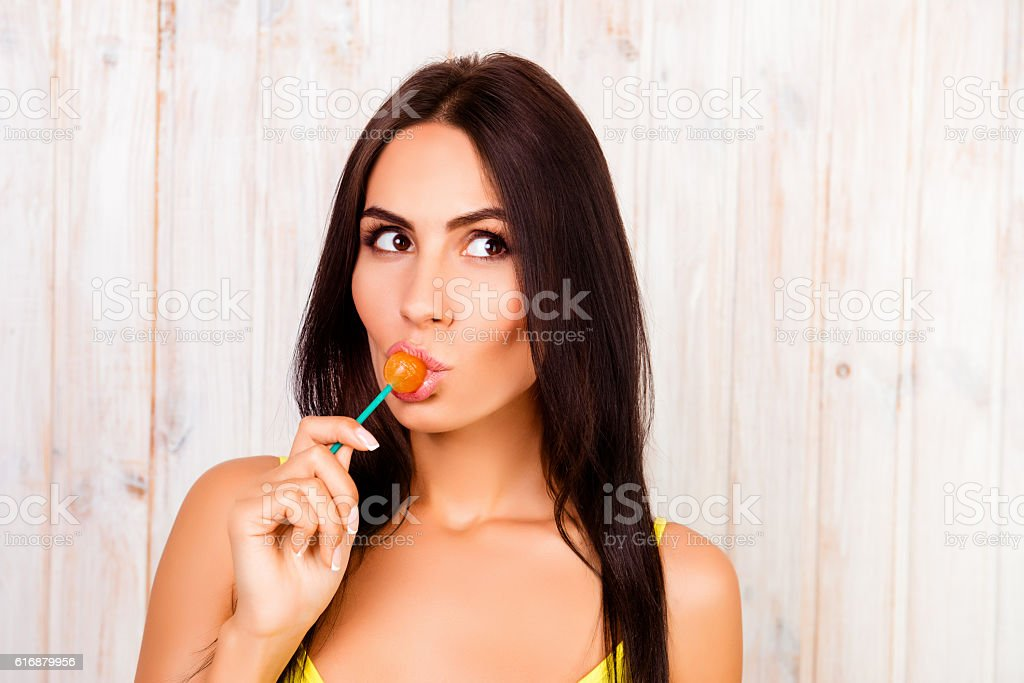 Portrait of beautiful young girl licking chupa chups stock photo