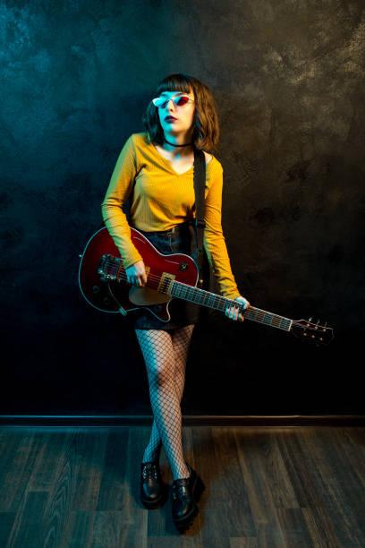 porträt der schönen jungen hipster-frau mit lockigen haaren mit roter gitarre in neonlicht. rockmusiker spielt elektrische gitarre. 90er-jahre-konzept. - bands der 90er stock-fotos und bilder