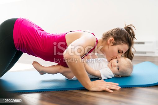 istock A Portrait of beautiful young mother in sports wear with her charming little baby in training session 1070026862