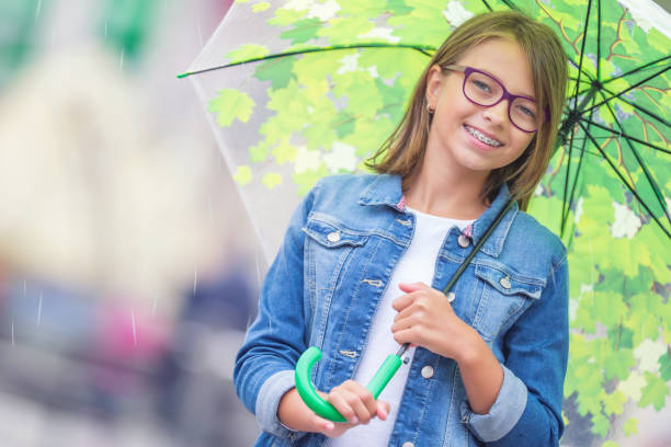 Portrait of beautiful young pre-teen girl with umbrella under spring or summer rain. Smilling girl with dental braces and glasses. stock photo