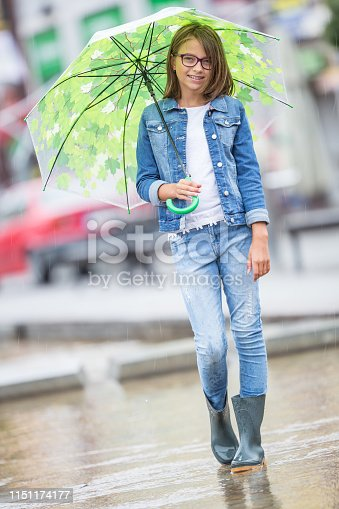 Portrait of beautiful young pre-teen girl with umbrella under spring or summer rain.